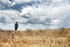 Hombre que camina en un campo Fotografía de archivo