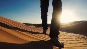 Hombre que camina en un cierre de Sahara Desert Dune para arriba almacen de metraje de vídeo