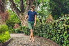 Hombre que camina en un pavimento de adoquín texturizado, Reflexology Guijarro s Fotos de archivo libres de regalías
