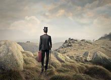 Hombre que camina en una montaña imagen de archivo