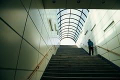 Hombre que camina encima de las escaleras en salida del subterráneo fotos de archivo