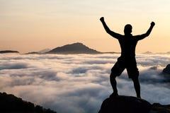 Hombre que camina la silueta que sube en montañas Fotografía de archivo libre de regalías