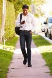 Hombre que camina a lo largo de la calle para trabajar escuchar la música fotografía de archivo libre de regalías