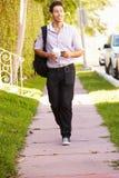 Hombre que camina a lo largo de la calle para trabajar escuchar la música foto de archivo