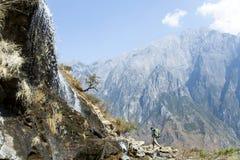Hombre que camina por la cascada de la ladera Fotografía de archivo libre de regalías