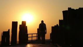 Hombre que camina sobre el puente de madera en la puesta del sol metrajes