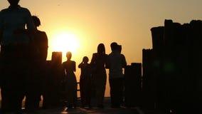 Hombre que camina sobre el puente de madera en la puesta del sol almacen de metraje de vídeo