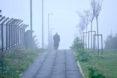 Hombre que camina solamente en tiempo de niebla Imagenes de archivo