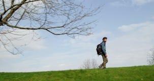 Hombre que camina a través del bosque que busca las fotos Lado de siguiente Varón adulto de la gente del backpacker milenario rea almacen de video