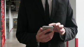 Hombre que camina y que consume Smartphone en la oficina, cierre almacen de video
