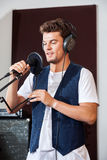 Hombre que canta mientras que sostiene el micrófono en estudio Imagenes de archivo
