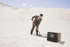 Hombre que cava por la caja fuerte en desierto foto de archivo libre de regalías