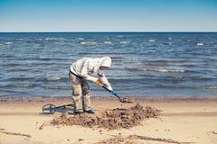 Hombre que cava un agujero en la playa Foto de archivo libre de regalías