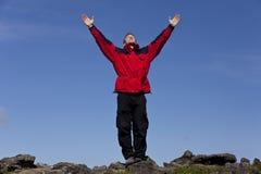 Hombre que celebra éxito encima de una montaña Imagen de archivo libre de regalías