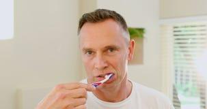 Hombre que cepilla sus dientes con el cepillo de dientes 4k almacen de video