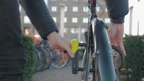 Hombre que cierra su bici almacen de metraje de vídeo