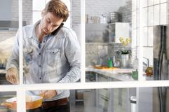 Hombre que cocina en la cocina que charla en el teléfono fotos de archivo