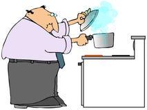 Hombre que cocina en una estufa Imágenes de archivo libres de regalías