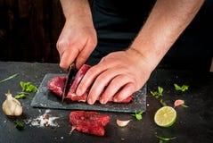Hombre que cocina la carne de la carne de vaca imagenes de archivo