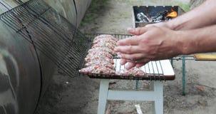 Hombre que cocina la carne en el fuego almacen de metraje de vídeo