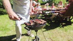 Hombre que cocina la carne en parrilla de la barbacoa en el partido del verano almacen de video