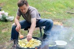 Hombre que cocina la carne sobre hoguera en el sitio para acampar Imagenes de archivo