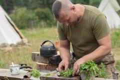 Hombre que cocina la carne sobre hoguera en el sitio para acampar Foto de archivo libre de regalías