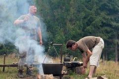 Hombre que cocina la carne sobre hoguera en el sitio para acampar Fotos de archivo