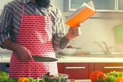 Hombre que cocina la ensalada y el libro de lectura sanos Imágenes de archivo libres de regalías