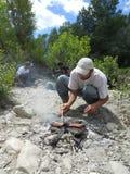 Hombre que cocina las salchichas en piedras Imagen de archivo libre de regalías
