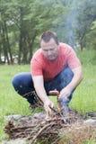 Hombre que cocina una salchicha Imagen de archivo libre de regalías