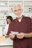 Hombre que coge los medicamentos de venta con receta en la farmacia Imagen de archivo libre de regalías
