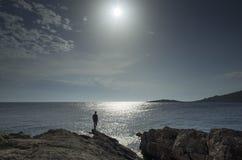 Hombre que coloca al aire libre en el cierre de piedra de la playa el mar adriático en Croacia en la puesta del sol Imágenes de archivo libres de regalías