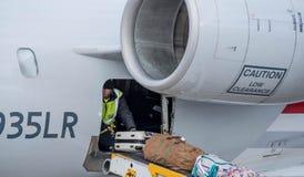 Hombre que coloca el equipaje en una banda transportadora del control del cargo del avión de pasajeros fotografía de archivo libre de regalías
