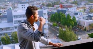 Hombre que come café en el balcón en casa 4k almacen de metraje de vídeo