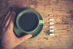 Hombre que come píldoras y café Imagen de archivo