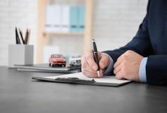 Hombre que completa formulario del seguro de coche fotos de archivo