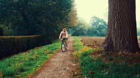 Hombre que completa un ciclo en un rastro en el parque del otoño bosque, humor triste, cámara móvil almacen de metraje de vídeo