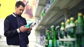 Hombre que compra agua mineral en el supermercado almacen de metraje de vídeo