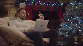 Hombre que compra un regalo para sí mismo en tienda en línea usando un ordenador portátil y una tarjeta de crédito en noche de la almacen de video