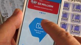 Hombre que comprueba el boleto de lotería por el app