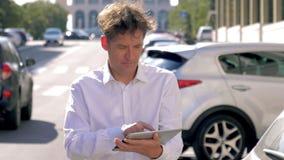 Hombre que comprueba el correo electrónico en la tableta en la calle de la ciudad con la cámara lenta del tráfico almacen de metraje de vídeo