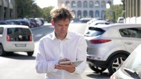Hombre que comprueba el correo electrónico en la tableta en la calle de la ciudad con la cámara lenta del tráfico metrajes