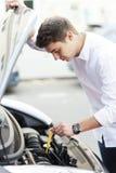 Hombre que comprueba el nivel de aceite en coche Imagen de archivo