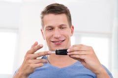 Hombre que comprueba la sangre Sugar Level Imagen de archivo libre de regalías