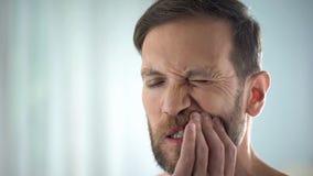 Hombre que comprueba los dientes delante del espejo, enfermedad dental, infección de la goma, pulpitis foto de archivo libre de regalías