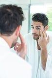 Hombre que comprueba ojos en espejo del cuarto de baño Fotos de archivo