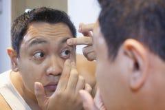 Hombre que comprueba su ojo en el espejo fotografía de archivo libre de regalías