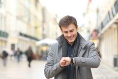Hombre que comprueba su reloj elegante en la calle fotos de archivo