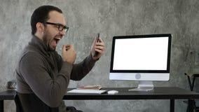 Hombre que comprueba sus dientes en la oficina cerca de la pantalla de ordenador Visualización blanca almacen de video